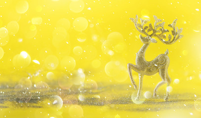 Silver glitter Christmas deer on yellow background with lights bokeh, copy space. Greeting card for new year party. Festive holiday concept. Banner