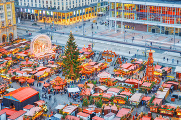Dresden Christmas Market in Germany, view from above on festive stalls and Christmas tree with carousel. Popular travel destination in Europe on Xmas Advent Holidays. Night illuminated view.