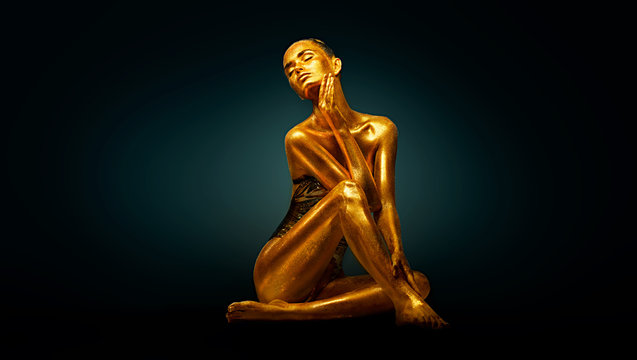High Fashion model girl with bright golden sparkles on her body posing, full length portrait of beautiful sexy woman with glowing body skin. Art design makeup