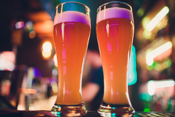 Two Glasses of Beer on a bar table. Beer Tap on background.