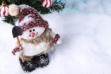 Cute handmade snowman on snow in front of a Christmas tree