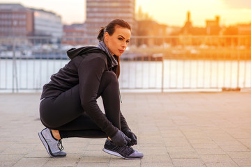 A sporty young woman tying her shoelace