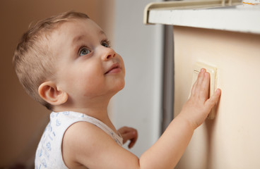 A small child, boy or girl, looking up and reaching to a light switch
