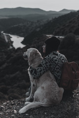 Young girl traveling by nature with backpack and dog