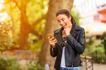 A happy young woman using her phone in a urban environment