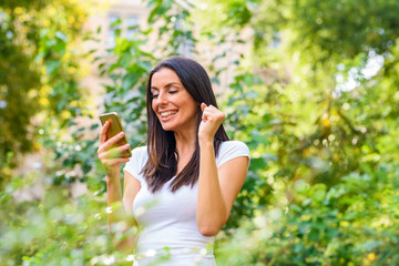 A cheerful woman in a Park receiving good news on her Smartphone