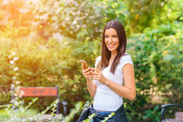 A cheerful woman in a Park using her Smartphone