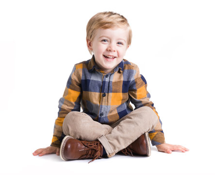 Adorable little kid seated on the floor, isolated over white bacground