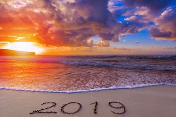 2019 inscription on wet beach sand