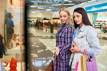 Positive young female friends in casual clothing holding shopping paper bags and discussing goods on shop window while finding Christmas gifts in mall