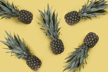 Pineapples on yellow background - Tropical fruits background