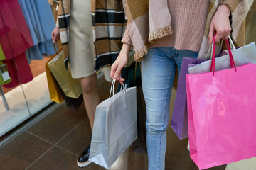 Close-up of two casual women walking and carrying shopping bags in their hands while doing shopping in store
