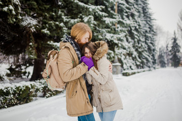 Date young couple in winter. Young Caucasian man with beard and long hair holding in hands the hands of girl with knitted gloves and warming and kissing them in snow park in winter is Valentines Day