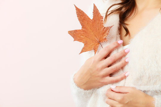 autumnal girl with maple leaf in hand