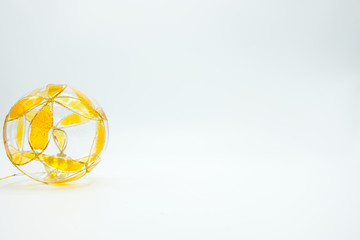 Transparent and yellow Christmas decoration bauble on white background.