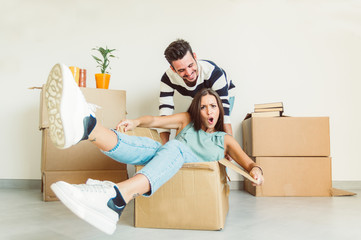 Happy couple having fun moving in the new house playing riding cardboards