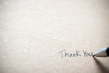 Hand writing thank you on piece of old grunge paper