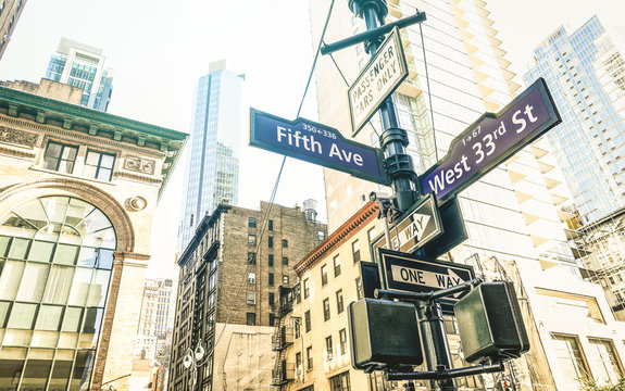 Street sign of Fifth Ave and West 33rd St in New York City - Urban concept and road direction in Manhattan downtown - American world famous capital destination on azure desaturated afternoon filter
