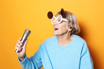 happy old woman with big eyeglasses holding a microphone and singing isolated on yellow background