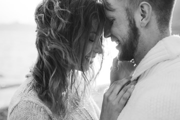 Close-up portrait of man and woman together, happy, looking at each other. Smiling, kissing and laughing. Black and white toning