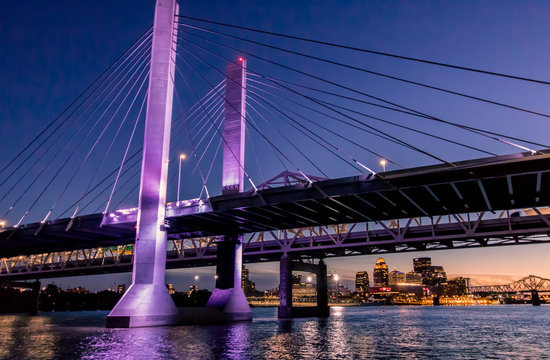 Louisville, Kentucky, USA downtown skyline from under the Abraham Lincoln bridge on the Ohio River at dusk.