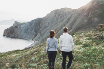 Young couple walking on nordic sea coast with mountain view in spring, casual style clothing sweaters and jeans