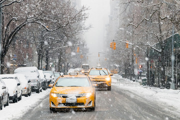 Taxis drive down a snow covered 5th Avenue during a winter nor'easter storm in New York City