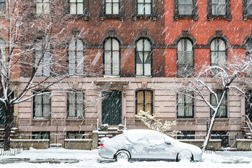 New York City winter street scene with snow covered car parked on Stuyvesant Street in the East Village