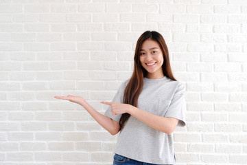 Portrait of young asian woman standing and smiling over white brick wall background