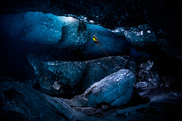 Ice climber abseiling into massive cavern in ice cave