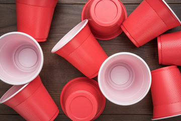 disposable plastic cups on the wooden background. top view of used plastic cups on the table. end of the party concept