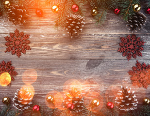 Old wooden background with fir branches adorned with cones. Space for text. Christmas card. Top view. Xmas holiday items. Light effect.