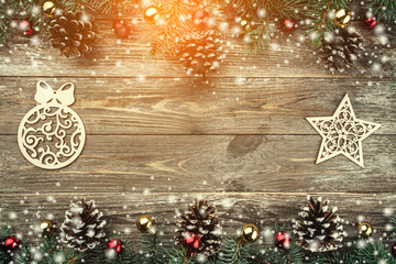 Old wooden background with fir branches adorned with cones. Space for text. Christmas card. Top view. Xmas holiday items. Effect of snow and light.
