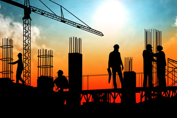 Silhouette illustration on group of builders are working on construction area site in sunset view.