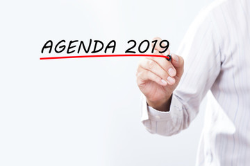 Businessman hand writing Agenda 2019 with red marker on transparent wipe board, Business concept.