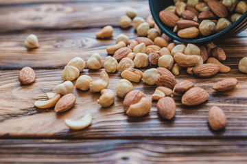 Wooden bowl with mixed nuts ontable. Healthy food and snack. Walnut, pistachios, almonds, hazelnuts and cashews.