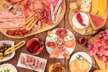 Charcuterie Tasting. A photo of many different sausages and hams, deli meats, and a cheese platter, shot from above on a rustic background with a glass of red wine, olives and grapes