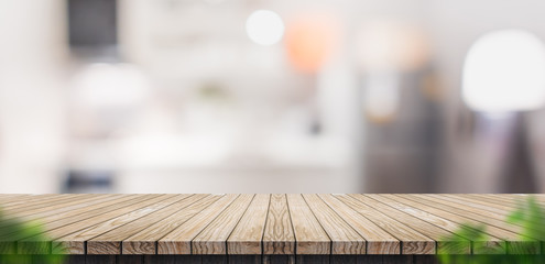 Empty brown wooden plank table top with blurred home kitchen with blur foreground leaf,Mock up template for display or montage of your design,Banner for advertise of product,panorama view,