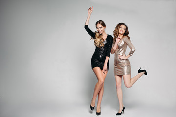 Studio portrait of two women dressed in mini evening dresses. Dancing at a party. The blonde raised her hand to the top, the brunette left leg bent at the calf. Dancing on the corporate. Isolated on a