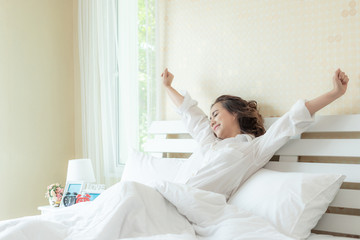 Beautiful Asian women smiling face stretching  after wake up enjoying sunny morning on the bed