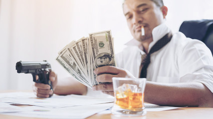 businessman at office  desk holding a gun and us dollar bill