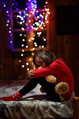 sad and tearful girl sitting with a teddy bear