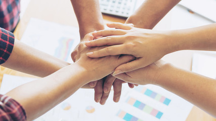 close up hand of business partnership people stacking hands finishing up meeting showing unity over office desk  , business teamwork concept