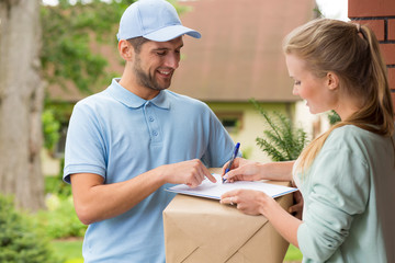 Happy courier in blue uniform and woman signing receipt of package delivery