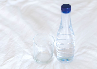 Closeup empty glass and water bottle drink on white bed, healthy care concept, selective focus