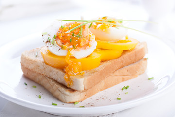 Boiled eggs on toasted bread with spices, paprika and spring onions on white background.