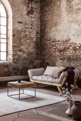 Wooden table on carpet in front of settee in loft interior with flowers and red brick wall. Real...