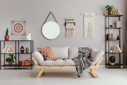 Macrame, mirror and ethno graphic on beige wall in stylish living room interior with metal furniture and comfortable couch and patterned pillow and blanket