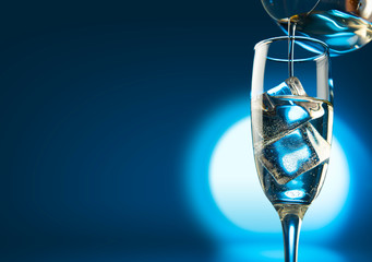 Champagne pouring in glasses with ice cubes