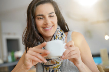 Smiling brunette girl drinking hot tea